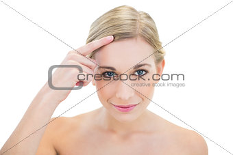 Content young blonde woman pointing her hair with her finger