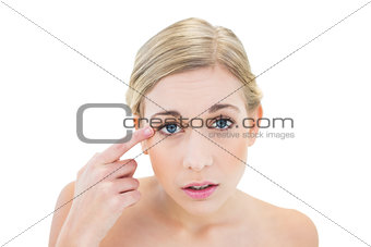 Anxious young blonde woman pointing her eye with her finger