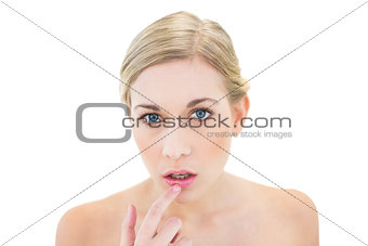 Stressed young blonde woman pointing her lip with her finger