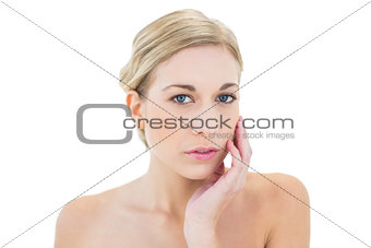Attractive young blonde woman posing touching her cheek