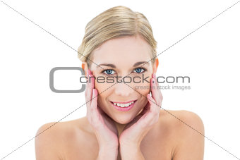 Pleased young blonde woman posing holding her head