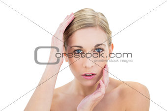Stern young blonde woman posing holding her head
