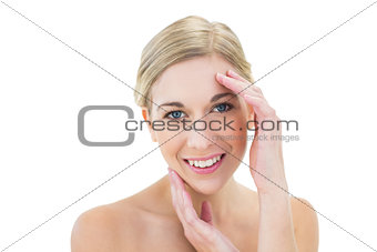 Happy young blonde woman touching her face