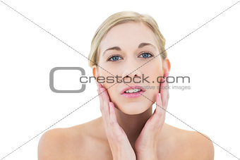Natural young blonde woman touching her cheeks