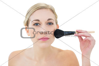 Natural young blonde woman applying powder on her cheek
