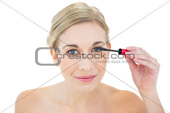 Smiling young blonde woman applying mascara