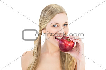 Pleased young blonde woman eating a red apple