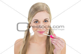 Amused young blonde woman applying gloss