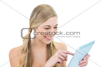 Amused young blonde woman using a tablet pc