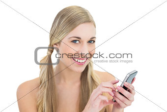 Delighted young blonde woman using a mobile phone
