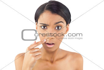 Gorgeous woman pointing at wrinkle above her lip