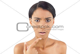 Worried woman pointing at wrinkle on her chin