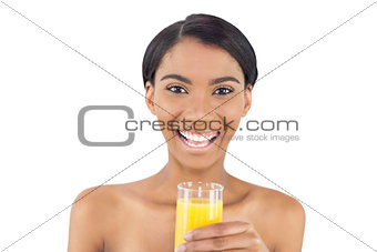 Smiling attractive model holding glass of orange juice