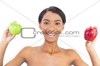 Smiling attractive model holding apples in both hands