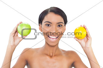 Smiling attractive model holding fruits in both hands