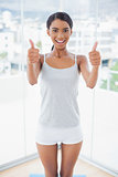 Attractive model in sportswear giving thumbs up to camera