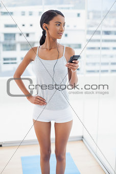 Thoughtful gorgeous model in sportswear listening to music