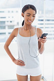 Happy attractive model in sportswear listening to music