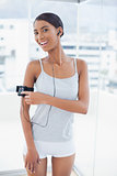 Smiling pretty model in sportswear changing song on her mp3
