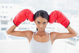 Serious competitive model wearing red boxing gloves