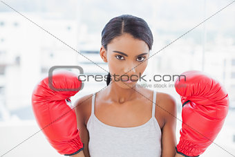 Serious competitive model with boxing gloves posing