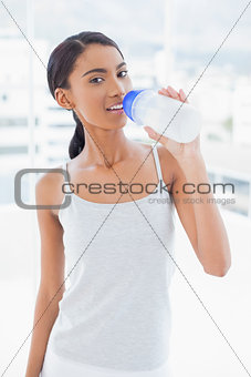 Smiling sporty model drinking water from her flask