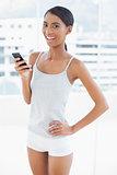 Happy sporty model using her smartphone