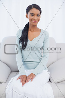Attractive woman sitting on cosy sofa