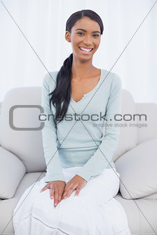 Smiling attractive woman sitting on cosy sofa