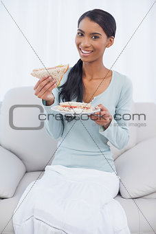Smiling attractive woman sitting on cosy sofa eating sandwich