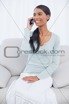 Smiling attractive woman sitting on cosy sofa having a phone call