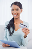 Happy attractive woman using her tablet pc to buy online