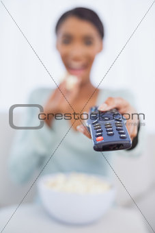 Attractive woman eating popcorn while watching tv