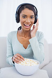 Attractive woman eating popcorn while listening to music