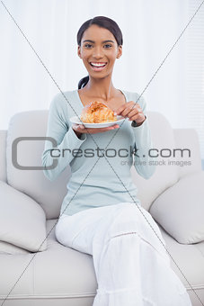 Smiling attractive woman eating croissant