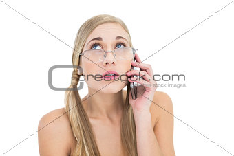 Anxious young blonde woman looking up while calling on phone