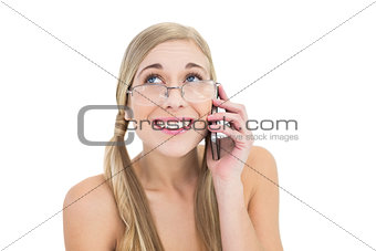 Embarrassed young blonde woman calling someone with her mobile phone
