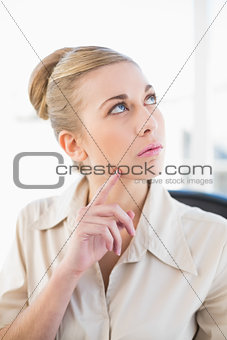 Thoughtful young blonde businesswoman looking up