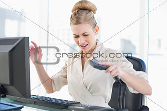 Angry young blonde businesswoman hanging up the phone