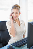 Smiling young blonde businesswoman calling with her mobile phone