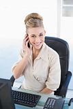 Cheerful young blonde businesswoman calling with her mobile phone