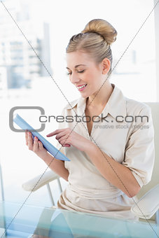Attentive young blonde businesswoman using her tablet pc