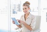 Pleased young blonde businesswoman using a tablet pc