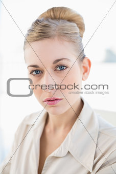 Attractive young blonde businesswoman looking at camera