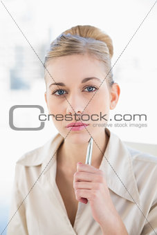 Meditative young blonde businesswoman looking at camera