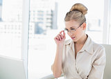 Thoughtful young blonde businesswoman looking over her glasses