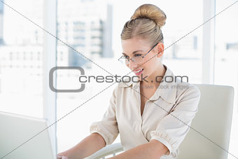Focused young blonde businesswoman using a laptop