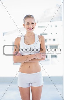 Cheerful young blonde model posing with crossed arms