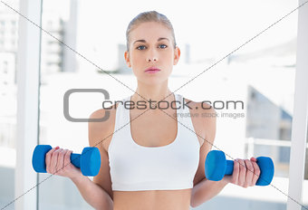 Attentive young blonde model exercising with dumbbells