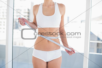Close up of a thin woman measuring her waist
